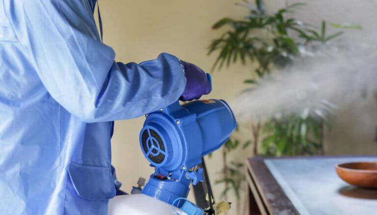 Professional cleaner in protective equipment uses electrostatic fogging machine