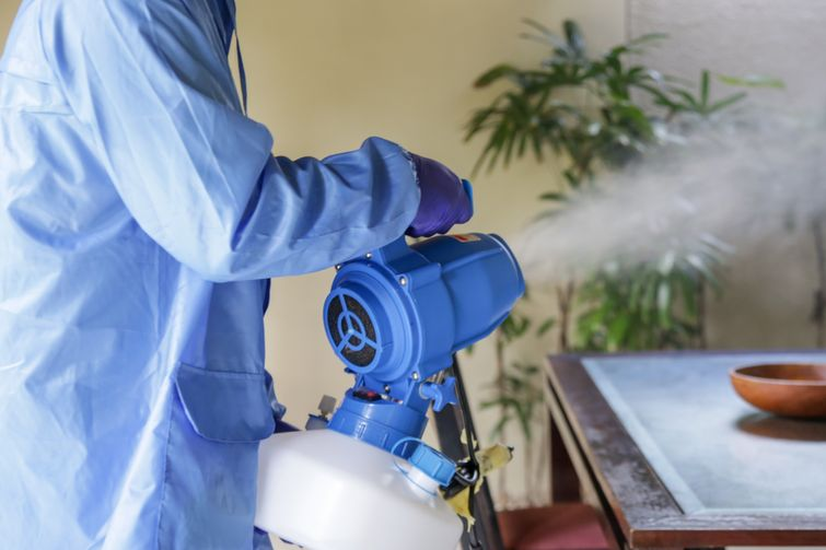 Cleaner in protective suit disinfecting Burlington dining room with fogger